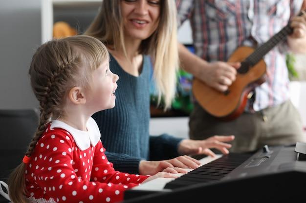 Родители учат дочь играть на музыкальных инструментах