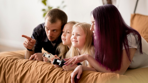 Parents teaching girls to play with joystick