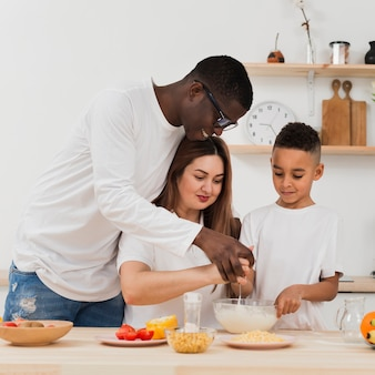 Parents teaching son to prepare food