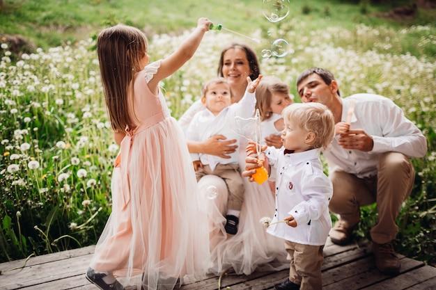 I genitori e i loro bambini giocano con i palloncini di sapone