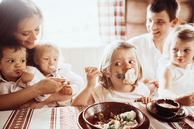 I genitori e i loro quattro figli ascoltano deliziosi vareniki