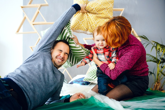 Parents and their little daughter play with pillows on the floor