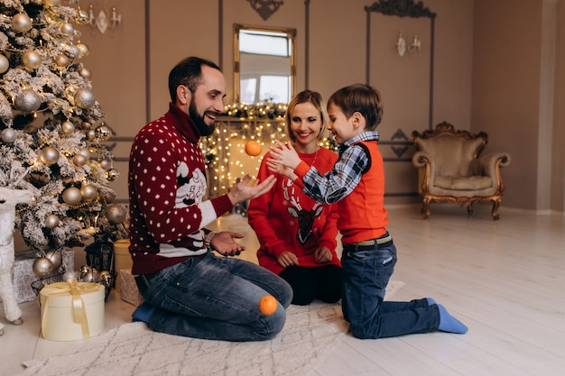 Parents and their little son in red sweater have fun with oranges sitting before a christmas tree