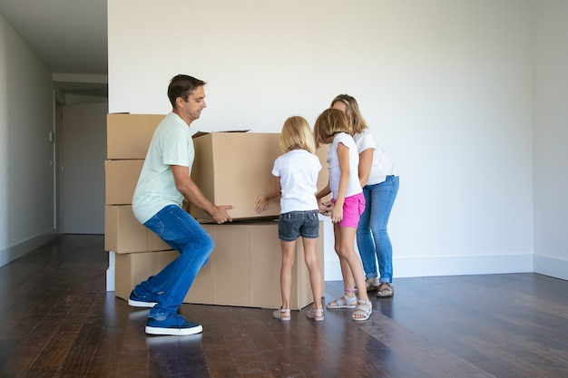 Parents and two girls carrying boxes and making stack carefully in their new empty flat