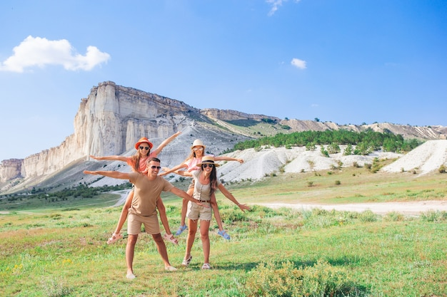 Parents and two kids with beautiful landscape on vacation