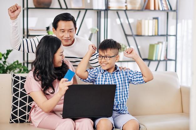 オンラインで幸せな興奮したプレティーンの息子へのプレゼントを注文するときにクレジットカードを使用している親