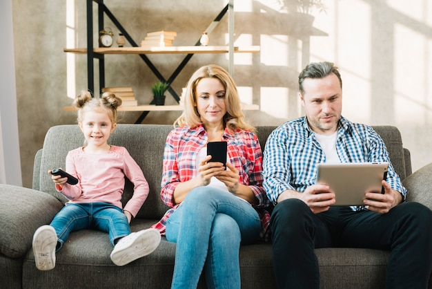 Parents using digital tablet and mobile phone while daughter watching television
