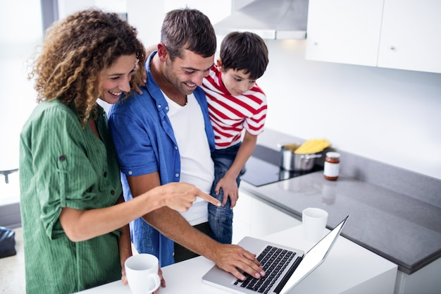 Parents using laptop with son in kitchen