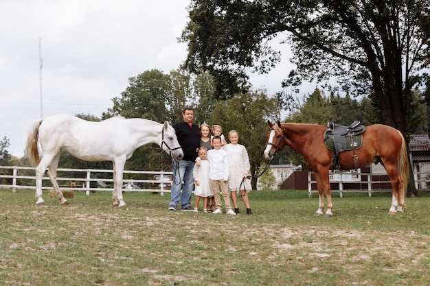 Parents walk with three little daughters and son near horses on farm on summer day. dad and mom spending time with children on holiday. happy family concept.