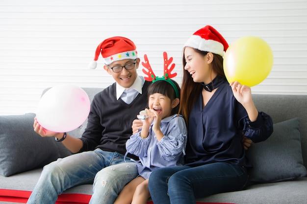 両親は赤いサンタ帽子を、娘は赤い枝角をつけています。彼らはタイ人です。アジアの人々は自宅のリビングルームでクリスマスのお祝いの雰囲気を楽しんでいます。