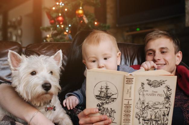 クリスマスで赤ちゃんとソファに座って犬を持つ親