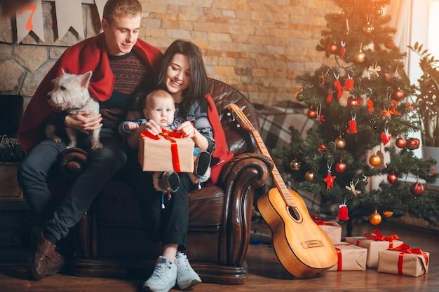犬と赤ちゃんとソファの上にギターの休憩を持つ親