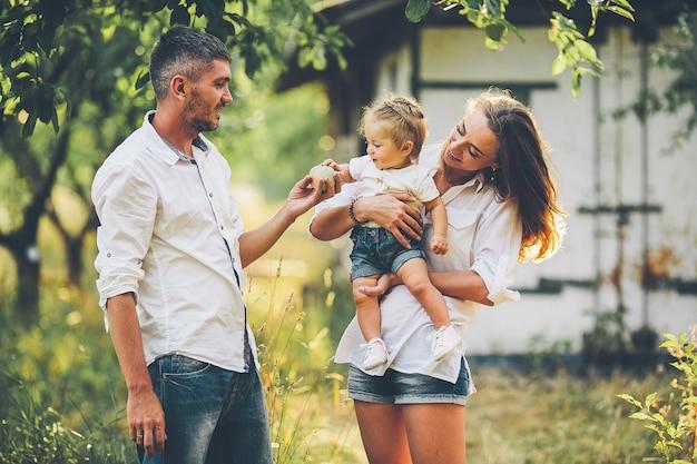 リンゴと桜の木のある農場でピクニックを楽しんでいる赤ちゃんを持つ親。