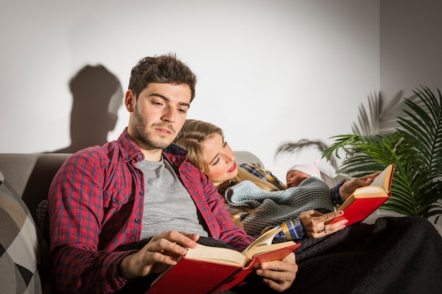 Parents with baby reading books in evening