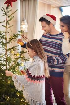 クリスマスの飾りをぶら下げている子供を持つ親