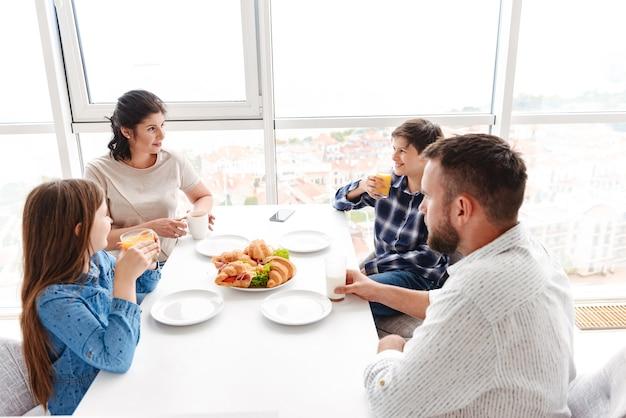 Родители с детьми 8-10 лет вместе завтракают на светлой кухне дома и едят бутерброды с круассанами