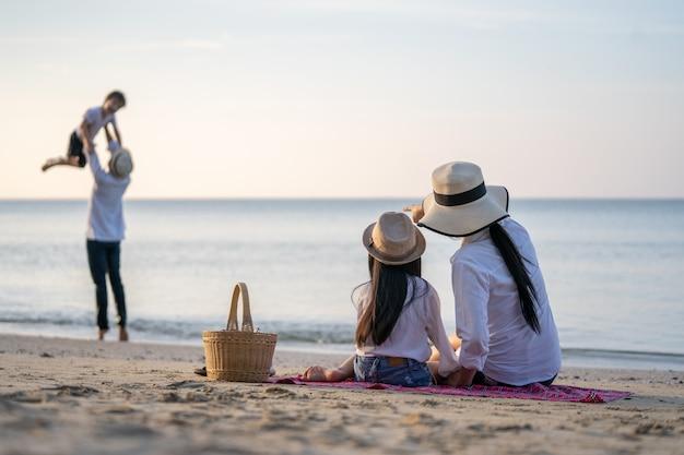 Premium Photo | Parents with children enjoying vacation on beach