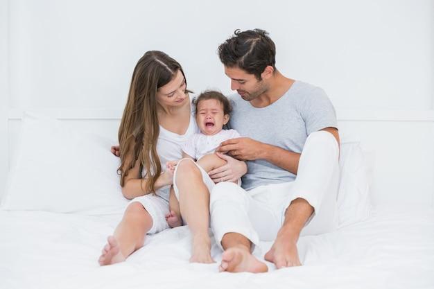 ベッドの上に座って泣いている赤ちゃんを持つ親