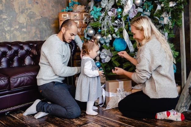 Parents with daugher decorate the christmas tree at home.