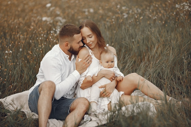 Parents with daughter. family in a field. newborn girl. woman in a white dress.