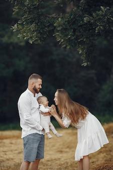 Genitori con figlia. famiglia in un campo. ragazza appena nata. donna in abito bianco.