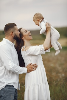 Родители с дочерью. семья в поле. новорожденная девочка. женщина в белом платье.