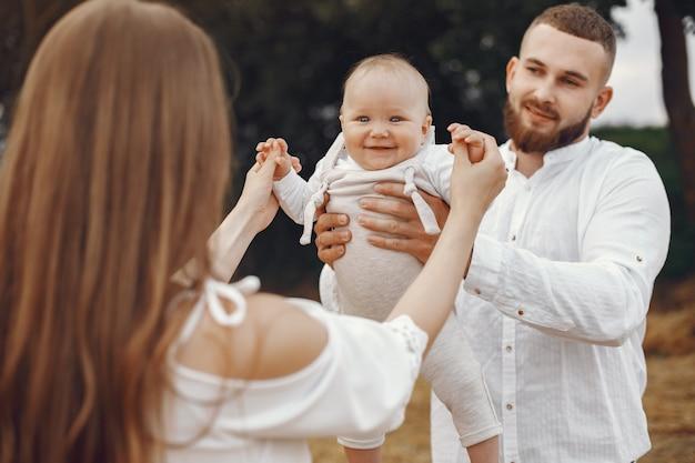 娘を持つ親。フィールドの家族。新生児の女の子。白いドレスを着た女性。
