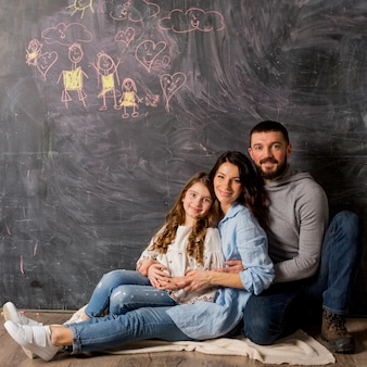 Parents with daughter hugging near blackboard with drawing