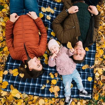 Parents with daughter lying on autumn leaves in park