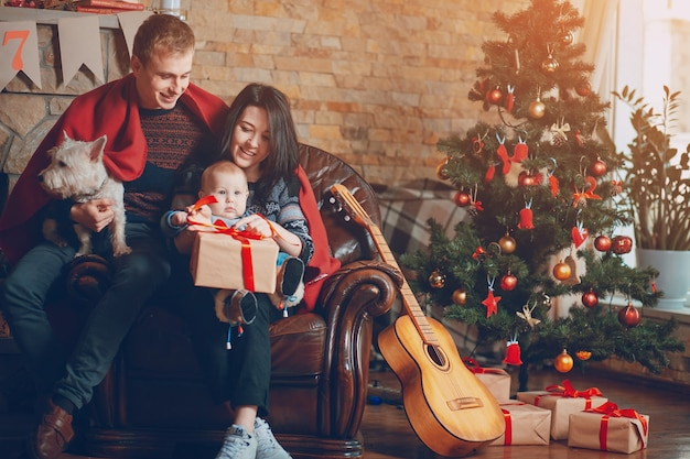 Parents with a dog and a baby and a guitar resting on the couch