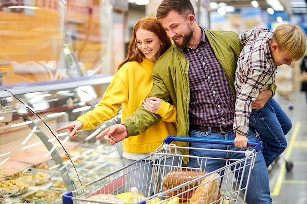 식료품 가게에서 불안한 아들이있는 부모, 남편이 음식을 진열장 근처에서 아들을 손에 쥐고있는 동안 저녁 식사를 위해 음식을 선택하는 여성