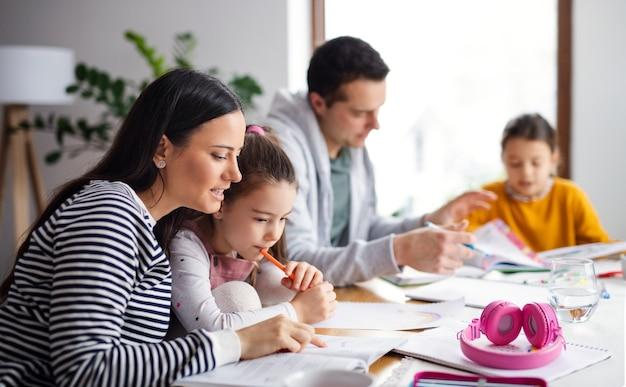 Родители с дочерьми школьницы в помещении дома, дистанционное обучение.