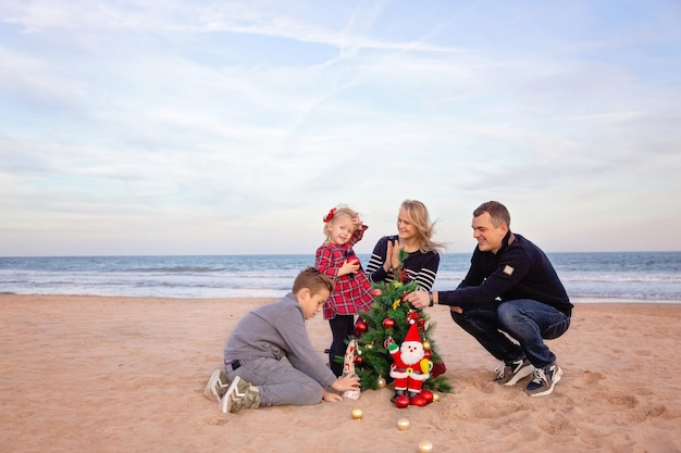 Parents with son and little daughter decorating christmas tree on the beach by the sea.