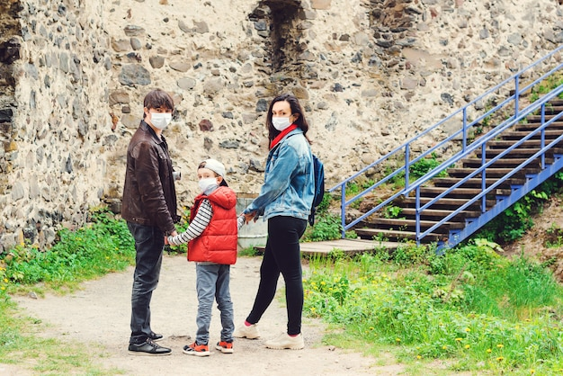 Parents with son wearing face masks outdoors. family trip to old castle. coronavirus quarantine.