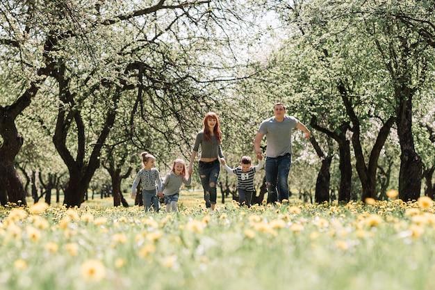 자녀를 둔 부모가 봄 정원에서 달리기 프리미엄 사진