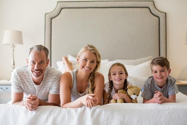 寝室のベッドに横になっている子供を持つ親