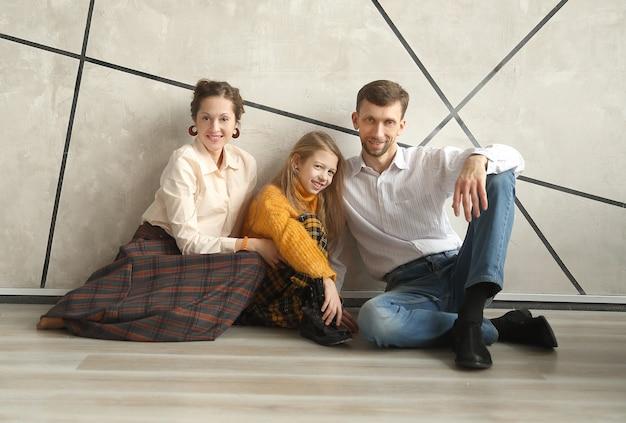 새 아파트에서 바닥에 앉아있는 어린 딸과 부모