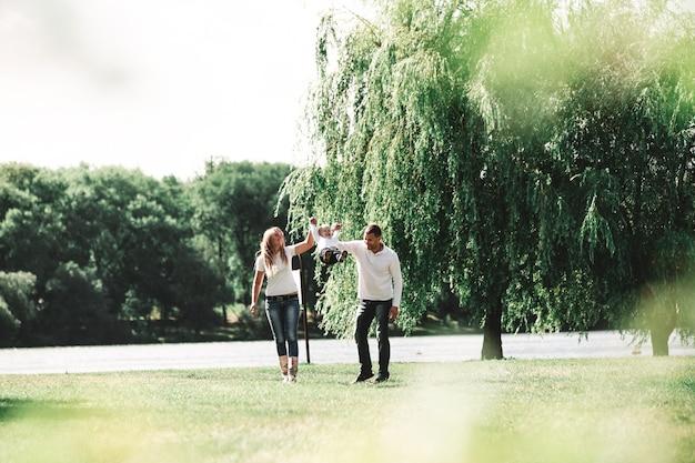Родители с маленьким сыном гуляют в весеннем парке