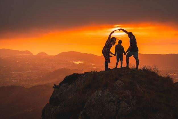 日没時に山の頂上に息子を持つ親