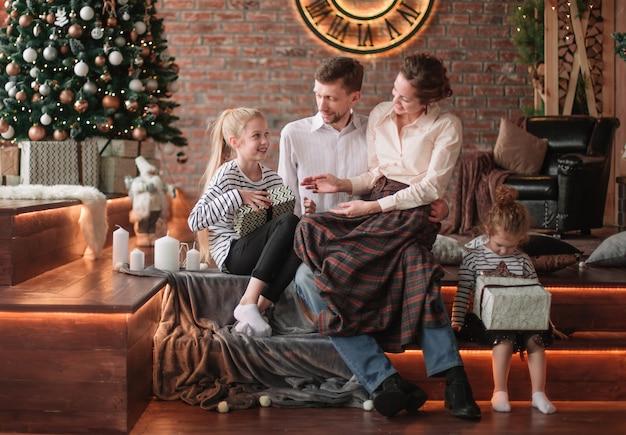 크리스마스를 위해 꾸며진 거실에 앉아 어린 자녀를 둔 부모.