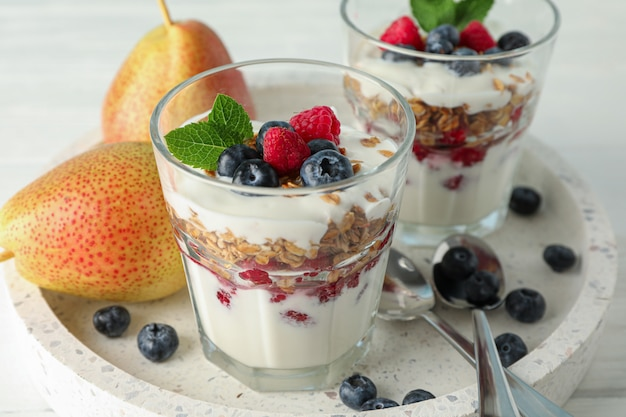 Parfaits and pears on white wooden table,