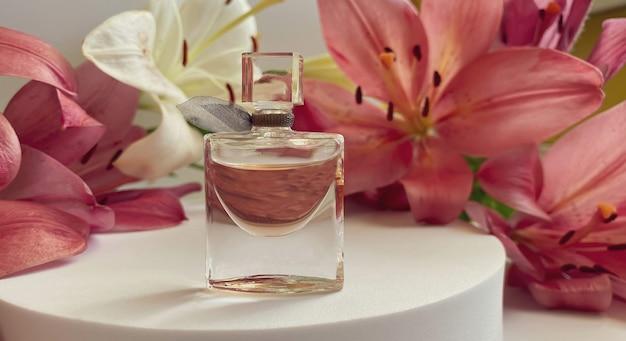 白い背景の花と香水。ピンクと白のユリの花びらに囲まれた香水瓶。オードトワレ、オードトワレ、美容コンセプト。