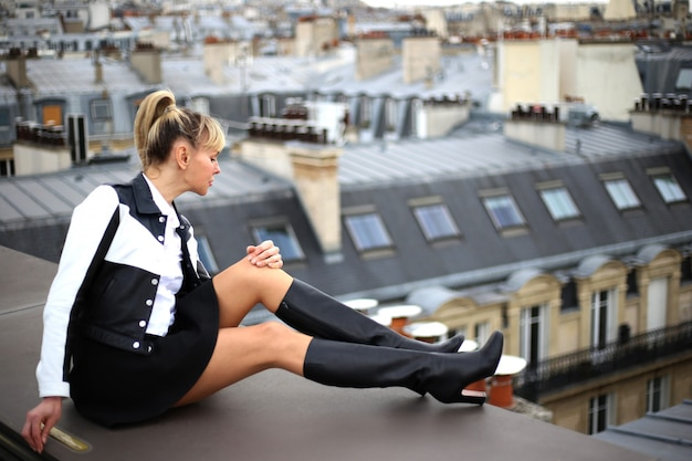 In paris beautiful young blond woman sitting at the roof in short skirt and high heel boots and look down