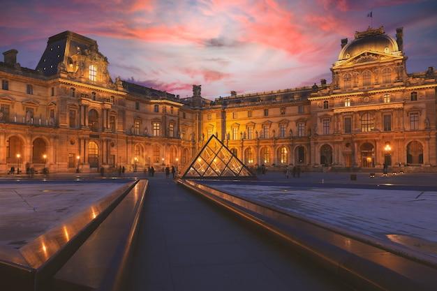 Париж - 26 декабря 2018: вид на здание лувра во внутреннем дворе вечером. лувр - один из крупнейших и самых посещаемых музеев мира.