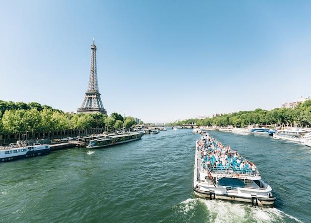 Париж, франция - 19 июня 2017 г .: вид на эйфелеву башню, вид с реки утром с голубым небом на заднем плане и лодкой, движущейся по реке сена