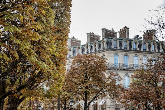 Paris mansion in autumn trees against a blue sky.
