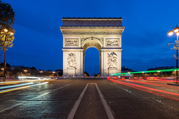 Paris street at night with the arc de triomphe in paris, france.