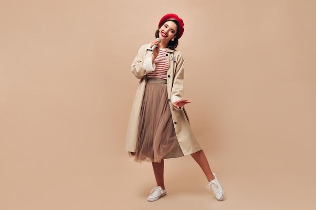 Signora parigina in berretto e trincea canta nel microfono. elegante bruna in gonna lunga e cappotto leggero autunnale in posa sulla macchina fotografica.
