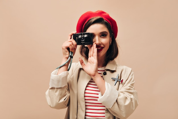 Parisian woman in beret takes photos on beige background. cute young girl with dark hair and bright lips in autumn coat holds black camera.