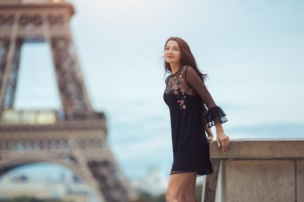 Parisian woman near the eiffel tower in paris, france.